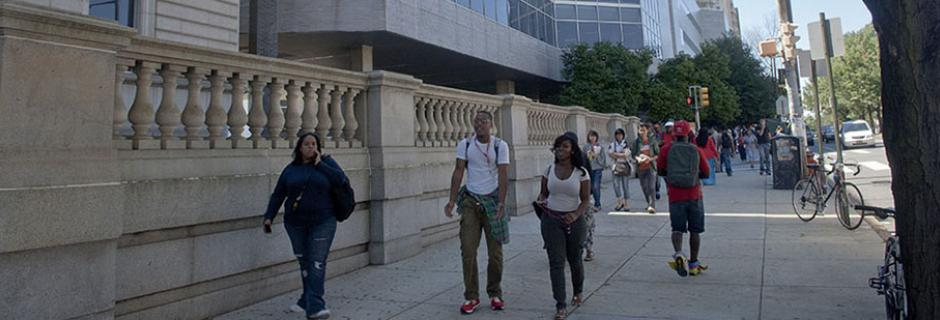 Students walking on Spring Garden Street in front of the Mint Building