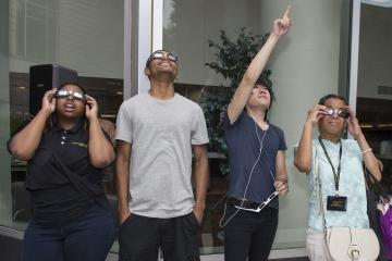 A group of students views the eclipse through eclipse glasses.