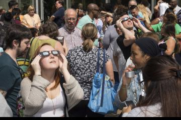 Two people in the crowd view the eclipse with eclipse glasses.