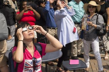 A person in the crowd views the eclipse with eclipse glasses.