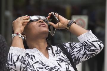 An Eclipse Party goer views the eclipse through eclipse glasses.
