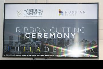 A TV monitor announces the ribbon cutting ceremony