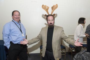 Faculty member Mark Kushner wears reindeer ears and smiles for the camera