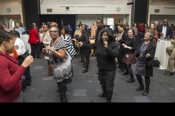 Attendees joining in a line dance