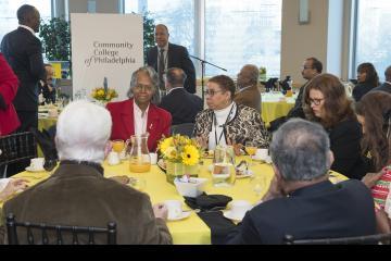 Attendees enjoy breakfast as Dr. Generals and Sulaiman Rahman prepare to speak