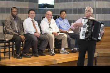 A panel member plays the accordion.