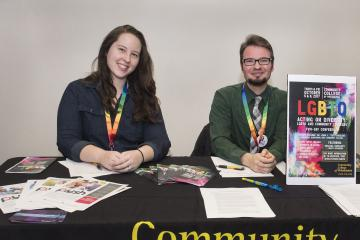 Greeters Kerri Grogan and Aiden Kosciesza  welcome attendees to the LGBTQ conference.