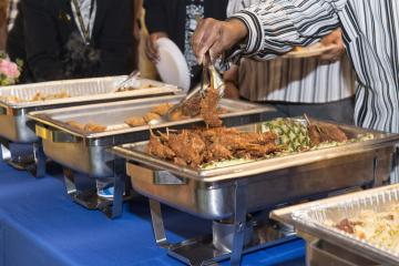 An attendee dishes chicken screwers
