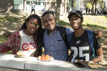 Students enjoying their food smile for the camera.