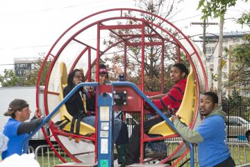"""Four brave souls prepare to go for a spin in one of the """"Tumbleweed,"""" a spinning ride."""