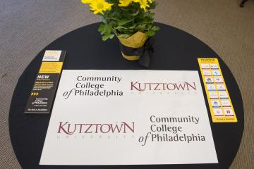 A table with signage for the Community College of Philadelphia and Kutztown University dual signing ceremony.