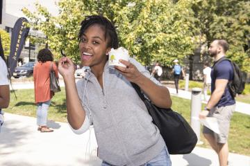 A student enthusiastically poses with her ice cream.