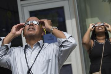 Dr. Generals, College President, views the eclipse through eclipse glasses.