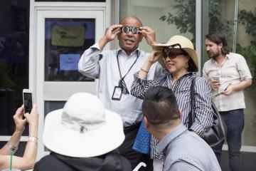 President Dr. Generals tries on a pair of eclipse glasses.