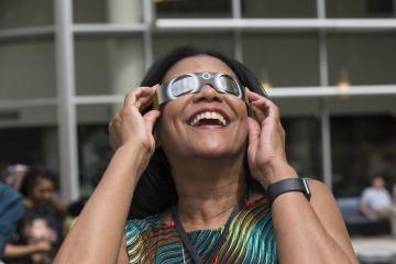 Vice President of Strategic Initiatives, Judy Gay, enjoys viewing the eclipse with eclipse glasses.