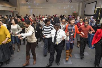 Attendees line dance