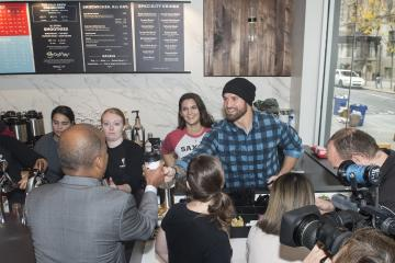 Eagles football player Chris Long serves Dr. Generals a coffee.