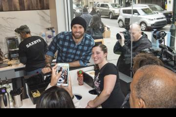 Chris Long and a customer pose for cameras.