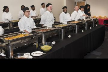 Culinary Arts students, smiling for the camera, prepare to serve a traditional Latin meal to guests.