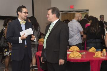 MC Nestor Torres speaks with Institutional Advancement VP, Greg Murphy at the luncheon.