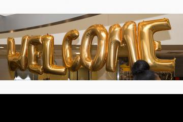 """Balloons spelling out """"Welcome"""" greet the students."""