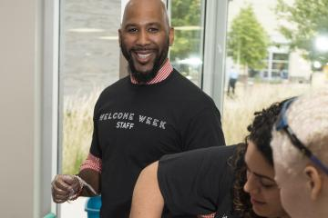 A Welcome Week Staff member smiles for the camera in between serving water ice.