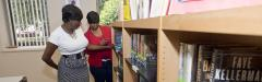 Women looking at books in library at Community College of Philadelphia.
